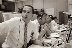 Spacecraft communicators are pictured as they keep in contact with the Apollo 11 astronauts during their lunar landing mission on July 20, 1969. From left to right are astronauts Charles M. Duke Jr., James A. Lovell Jr. and Fred W. Haise Jr.